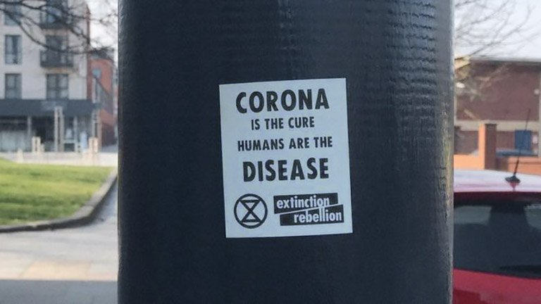 An image of a fake Extinction Rebellion sticker with a message on the Covid-19 pandemic that conveys eco-fascist themes, that was posted by a now-suspended Twitter account. The stickers were left on lampposts in Bedford and Brighton. (Twitter)