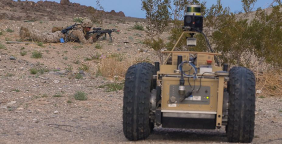 A US Marine Corps infantryman sets up a firing position while covered by an unmanned ground vehicle during field drills for DARPA's Squad X programme, held at the Air Ground Combat Center in Twentynine Palms, California. (DARPA)