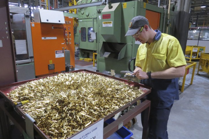Patrick Warner, an employee at Thales Australia, examines cartridge cases for 5.56 mm ammunition, part way through the manufacturing process at the Benalla, Victoria, production line. (Australian Department of Defence)