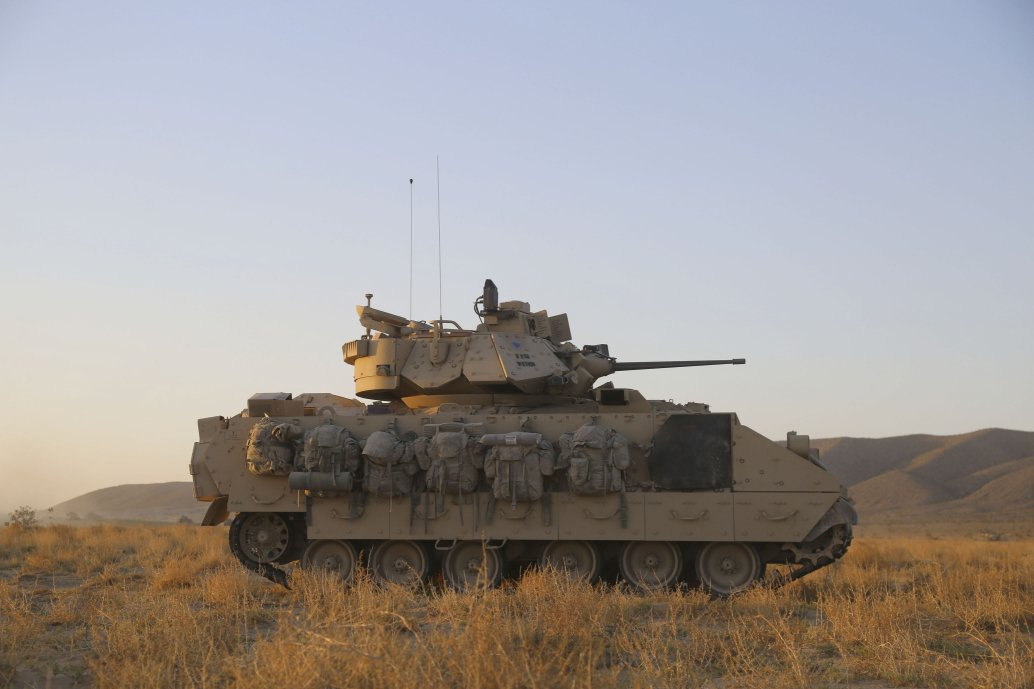 An M2A2 Bradley observes the terrain for enemy elements during training at Fort Irwin, California, in May 2018. The US Army has tasked BAE Systems with refitting two A2 Bradley vehicles with hybrid electric drives. (US Army/PFC Antoine Rolle)