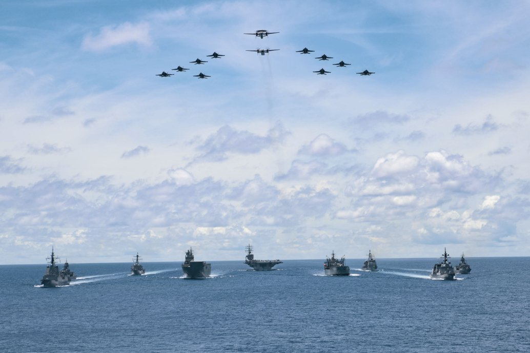 "As aircraft from Carrier Air Wing 5 fly overhead, US Navy ships USS         Ronald Reagan         ,         Antietam,         and         Mustin         are seen here on 21 July taking part in a trilateral passage in the Philippine Sea with Royal Australian Navy ships         Canberra         ,         Hobart         ,         Stuart,Arunta,         and         Sirius         and Japan Maritime Self-Defense Force Akizuki-class destroyer JS         Teruzuk         i on their way to the 2020 edition of the multinational 'Rim of the Pacific' (RIMPAC) exercise in Hawaii. Washington reiterated that same day that it will continue to bolster its ""growing network of Indo-Pacific allies and partners"", referring to US partnerships in the region as ""a strategic advantage our competitors cannot match"".        (Commonwealth of Australia 2020)"