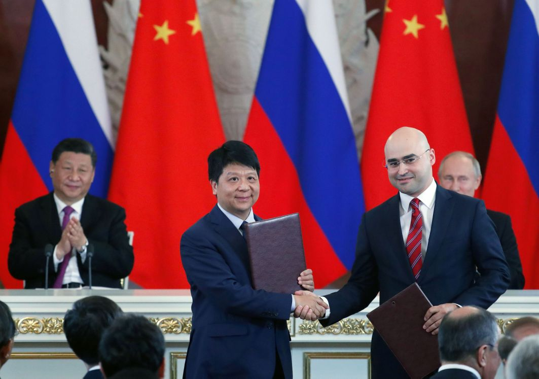 Chinese President Xi Jinping (left, rear) and Russian President Vladimir Putin (right, rear) applaud as Guo Ping (centre), Deputy Chairman of the Board and Rotating Chairman of Huawei, shakes hands with Alexei Kornya, President and CEO of Russian mobile phone operator MTS, during a signing ceremony following Chinese-Russian talks at the Kremlin in Moscow on 5 June 2019. (Maxim Shipenkov/AFP via Getty Images)