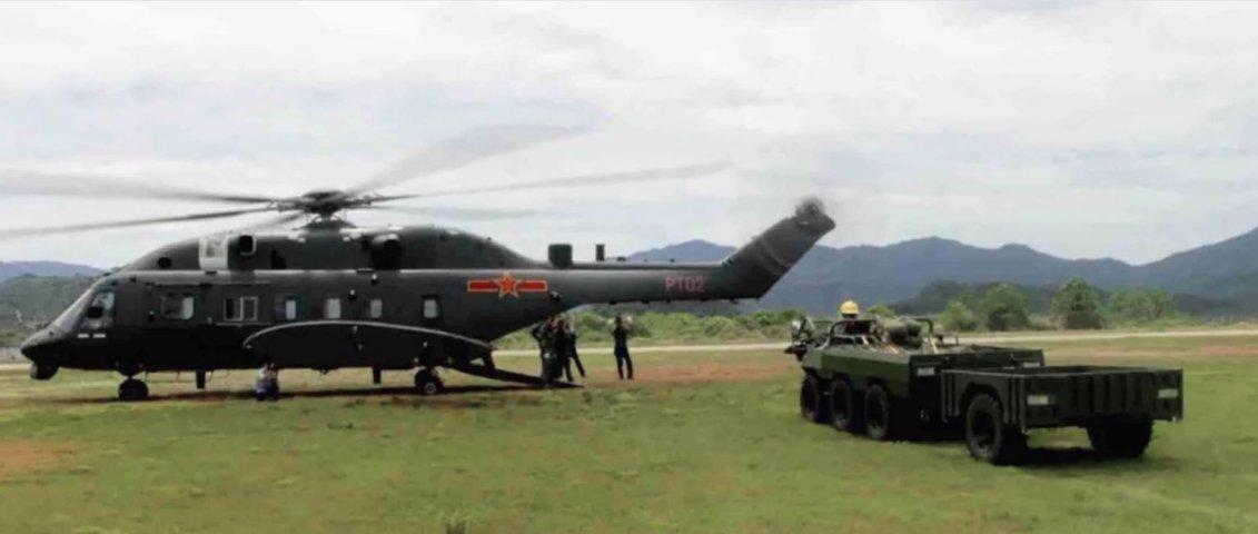 Una captura de pantalla de imágenes de CCTV que muestra la variante de cuerpo ancho del helicóptero de elevación media CAIG Z-8G poco antes de realizar pruebas de transporte de carga con el vehículo todoterreno que se ve al lado.  (A través de cctv.com)