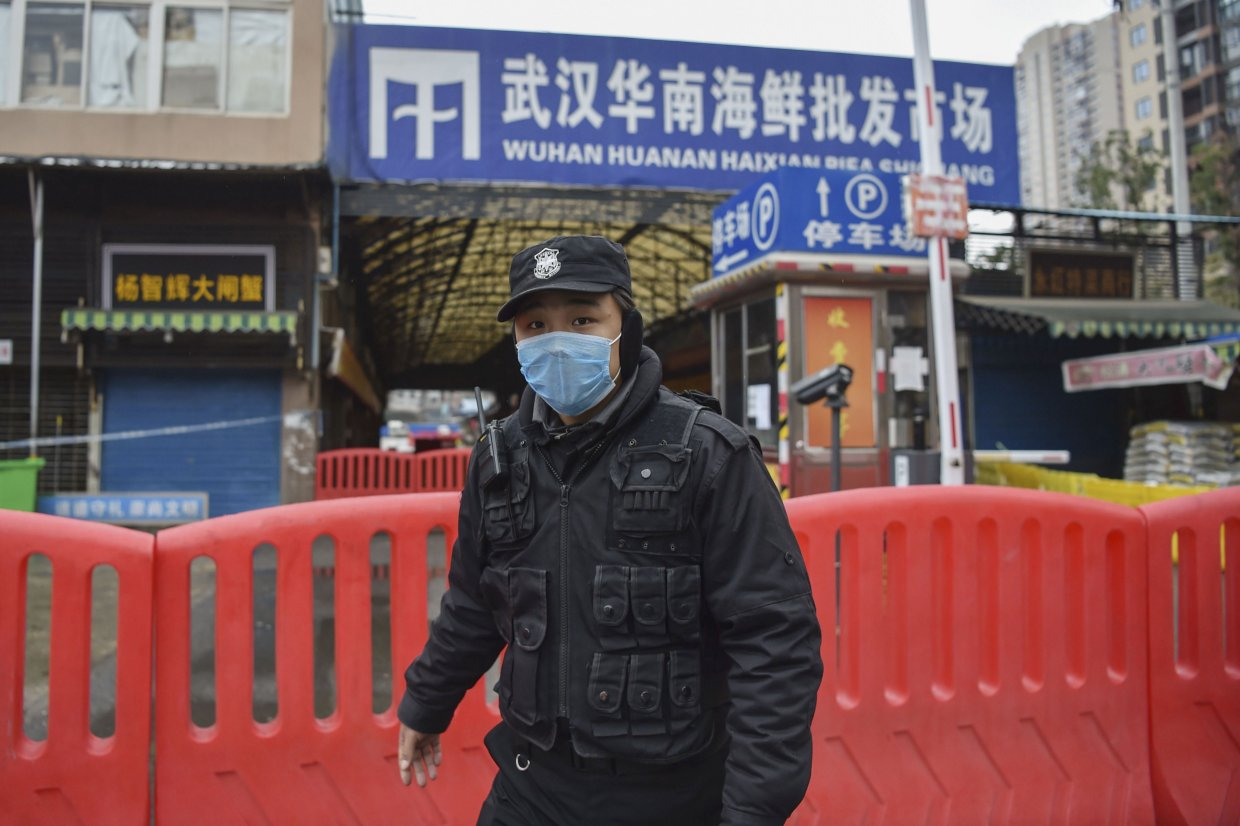 A police officer stands guard on 24 January 2020 outside the Huanan Seafood Wholesale market where the coronavirus was detected in Wuhan, China. At the time, the virus's death toll stood at 25, rising to more than 816,000 by 25 August. (Hector Retamal/AFP via Getty Images)