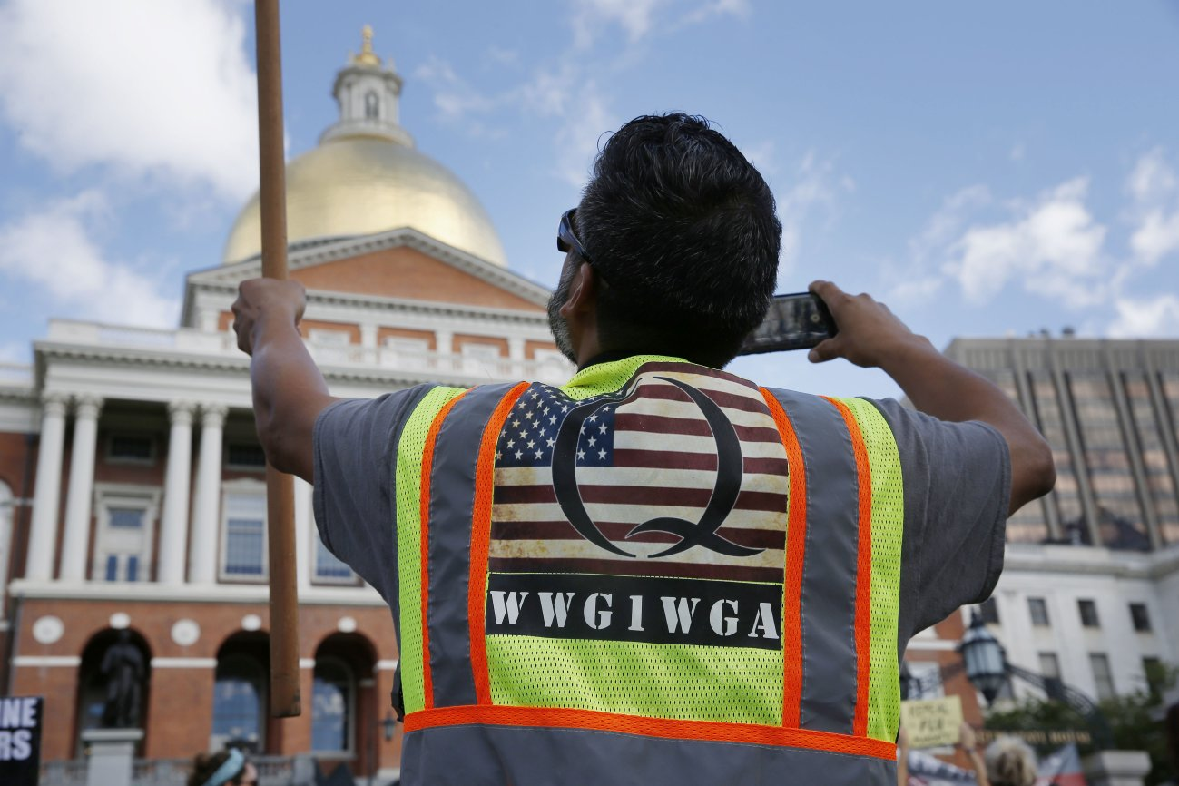 A demonstrator wearing a QAnon vest attends a 'No Mandatory Flu Shot' rally outside the State House in Boston, Massachusetts, on 30 August 2020. The acronym on his bib, WWG1WGA, is a common QAnon rallying cry, meaning 'Where We Go One, We Go All'. (Jessica Rinaldi/The Boston Globe via Getty Images)