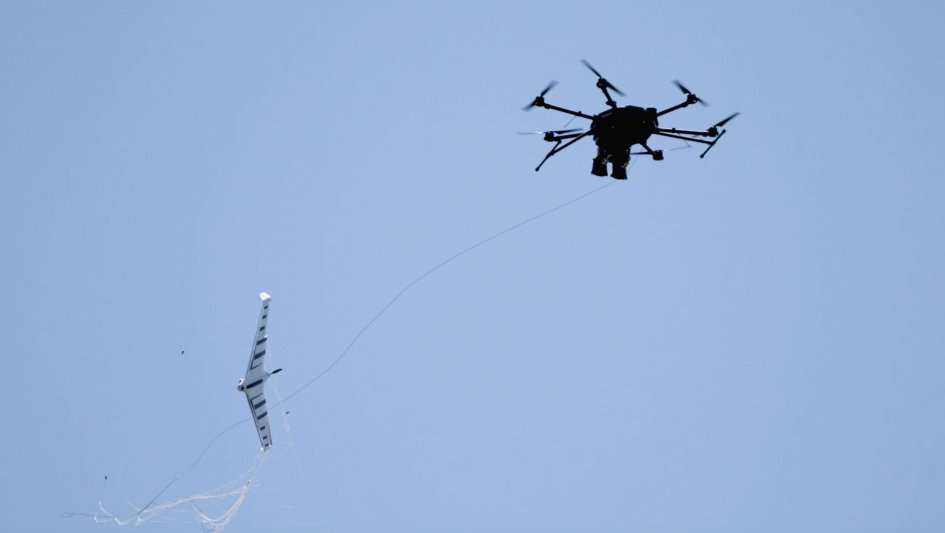 Fortem Technologies' DroneHunter UAS (right) uses its NetGun net attached to a tether to capture an enemy UAS. (Fortem Technologies)