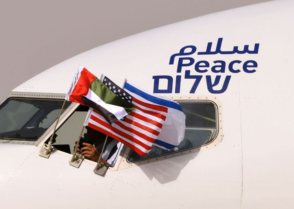 Emirati, Israeli, and US flags are attached to an El-Al aircraft with the word 'peace' written in Arabic, English, and Hebrew. The flight arrived at Abu Dhabi airport – the first commercial flight from Israel to the UAE – on 31 August 2020. (Karim Sahib/AFP via Getty Images)
